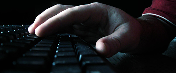 A hand on a black keyboard